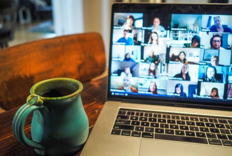 a mug beside a laptop having a virtual meeting